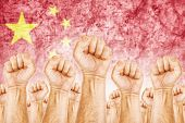 stock photo of labourer  - China Labour movement workers union strike concept with male fists raised in the air fighting for their rights Chinese national flag in out of focus background - JPG