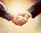 Business people shaking hands against sunny sky background in vintage mood. Conceptual handshake