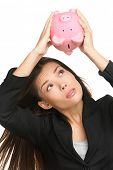 Empty piggy bank. Money debt, bankruptcy and lost savings concept. Business woman or banker showing empty pink piggy bank isolated on white background.