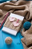 picture of blanket snow  - One old notebook in knitted cover with felt hearts lie next to the coil bright filaments and blanket knitted on blue background - JPG