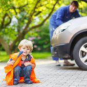 Little Boy In Orange Safety Vest During His Father Repairing Family Car