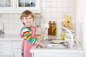 Happy Little Blond Kid Boy Washing Dishes In Domestic Kitchen