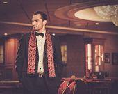 picture of gambler  - Handsome man wearing suit in luxury casino interior  - JPG