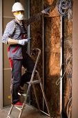 image of electrician  - Electrician working with wires in new apartment on a ladder  - JPG