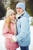 Young couple in winterwear looking at camera in park