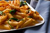 stock photo of vodka  - Penne pasta in creamy vodka tomato sauce with sauteed baby spinach leaves - JPG
