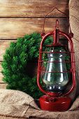 Kerosene lamp with wreath on wooden planks background