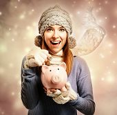 Happy Young Woman Depositing Money Into Her Piggy Bank