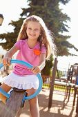 picture of seesaw  - Young Girl Having Fun On Seesaw In Playground - JPG