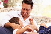 stock photo of tickle  - Father At Home Sitting On Outdoor Seat And Playing With Son - JPG