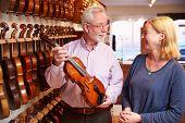 Salesman Advising Customer Buying Violin