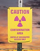 Contamination area warning sign with orange sunrise.