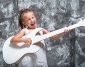 beautiful little girl in white dress with her guitar