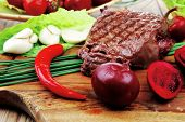 meat savory : beef grilled and garnished with green lettuce and red chili hot pepper on wooden table with cutlery