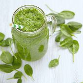 Apple and spinach smoothie in glass on a wooden background