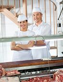 Portrait of confident male and female butchers standing at meat counter in shop