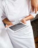 Midsection of male and female butchers using digital tablet in store