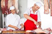 Mature male and female butchers working together at counter in butchery