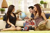 Young companionship planning summer holiday, poiting destinations on globe.