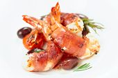 Shrimps with bacon, olives and rosemary in white plate, close-up