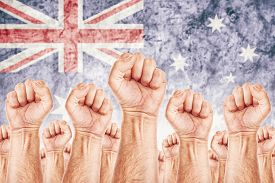 stock photo of labourer  - Australia Labour movement workers union strike concept with male fists raised in the air fighting for their rights Australian national flag in out of focus background - JPG