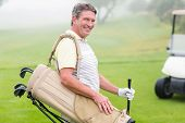image of buggy  - Happy golfer with golf buggy behind on a foggy day at the golf course - JPG