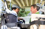 stock photo of buggy  - Golfing friends driving in their golf buggy smiling to each other at golf course - JPG