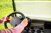 foto of buggy  - Golfer driving his golf buggy forward at the golf course - JPG