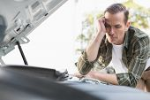 image of upset  - Upset man checking his car engine after breaking down in a car park - JPG