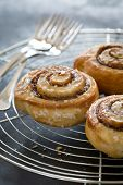 stock photo of cinnamon  - Freshly baked cinnamon buns on rustic baking plate - JPG