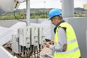 foto of electrical engineering  - Mature engineer on building roof checking solar panels - JPG