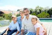picture of swimming pool family  - Happy family sitting by private swimming - JPG