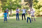 stock photo of extended family  - Extended family playing with hula hoops on a sunny day - JPG
