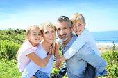 stock photo of piggyback ride  - Parents giving piggyback ride to kids by the sea - JPG