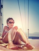 stock photo of sun-tanned  - Sexy woman on sailboat lying down on the deck of luxury sailboat - JPG