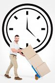 pic of trolley  - Delivery man pushing trolley of boxes against clock - JPG