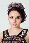 foto of brunete  - portrait of a girl brunete with hair beam with a delicate make up and a wreath in her hair from black roses with thorns rock - JPG