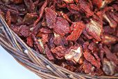 picture of stall  - Dried tomatoes in a wicker basket on a market stall  - JPG