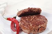pic of pepper  - fresh juicy beef meat hamburger with dry pepper on white plate over tablecloth with cutlery - JPG