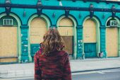 pic of board-walk  - A young woman is walking on the street in a city and is looking at a boarded up building - JPG