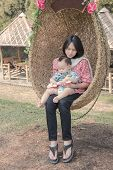 picture of mother baby nature  - young mother holding baby on rattan swing - JPG