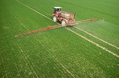 foto of tractor  - Aerial view of the tractor spraying the chemicals on the large green field - JPG