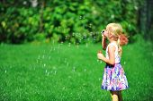 pic of blowers  - little girl play with bubble blower on green lawn - JPG