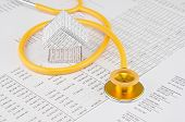 stock photo of coil  - Yellow and gold stethoscope coil house place on finance account - JPG