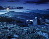 pic of roof-light  - composite mountain landscape with ancient fortress with high stone walls and red roof among the woods and huge boulders on a hillside at night in full moon light - JPG