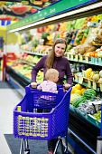 picture of grocery store  - Vertical photo of young mother and her baby daughter shopping in supermarket - JPG