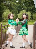 image of cross-dress  - Two young beautiful girl in irish dance dress and wig posing outdoor - JPG