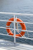 foto of passenger ship  - Orange colored lifebelt and rope hang on a white banister a passenger ship - JPG