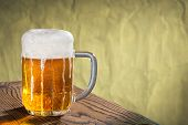 picture of suds  - glass of beer with brown unfocused background - JPG