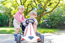 pic of pedal  - Two little blond friends boys having fun with pedal car in home - JPG